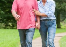 Active and happy senior couple walking in the park